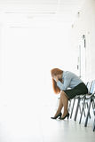 Side view of frustrated businesswoman sitting on chair in office Stock Photo