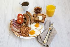 Side view, full english breakfast with fried eggs, sausages, bacon, beans and toasts. White wooden background. Close-up Stock Image