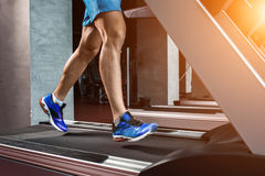 Side view full length of young man in sportswear running on treadmill at gym. Muscular young man in blue shorts doing exercises. Part of the body. Only legs Stock Photography
