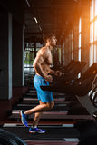 Side view full length of young man in sportswear running on treadmill at gym Stock Images