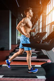 Side view full length of young man in sportswear running on treadmill at gym. Muscular young man in blue shorts doing exercises. sun flare Royalty Free Stock Photography