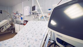 Side view of a fully-equipped hospital ward with a focus on a bed and a monitor stock video footage