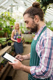 Side view of gardener using digital tablet at greenhouse Stock Photo