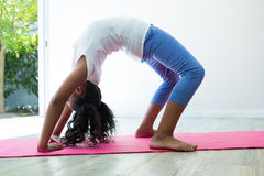 Side view of girl bending over backwards while exercising Stock Images