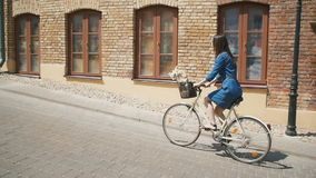 Side view of a girl cycling up the road with flowers in a basket and exploring the city, slow mo, steadicam shot. Side view of a brunette girl with long hair stock video footage