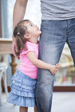 Side view of girl hugging father's leg in house stock image