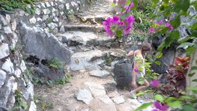 Side view girl goes down stone steps leading to yard. Side view girl with long plait in denim shorts goes down old stone steps leading to temple yard among stock video footage