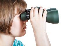 Side view of girl looks through binoculars Royalty Free Stock Image