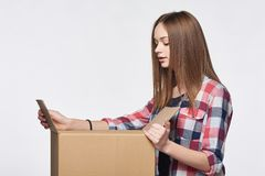 Side view a girl opening a box Royalty Free Stock Photo