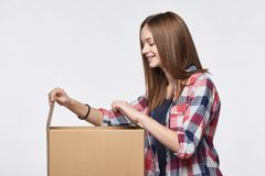 Side view a girl opening a box Royalty Free Stock Photos