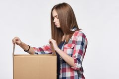 Side view a girl opening a box Royalty Free Stock Images