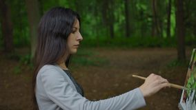 Side view of a girl painting a landscape in a forest. Beautiful brunette leads with a brush on a canvas on an easel. Drawing in the open air. Middle slow stock footage