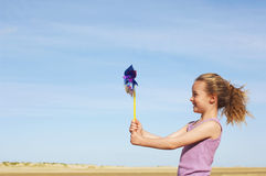 Side View Of Girl With Pinwheel On Beach Royalty Free Stock Photos
