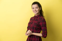 Side view of girl in red checkered dress against yellow backgrou Stock Photography