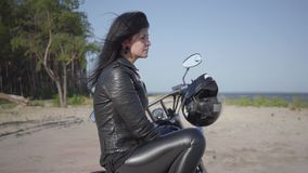 Side view of the girl sitting on the motorcycle looking away on the riverbank. Hobby, traveling and active lifestyle. Female biker outdoors on the motorbike stock video footage