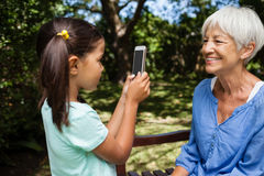 Side view of girl taking photograph of grandmother sitting on bench Stock Images