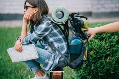 Side view of girl traveler holding map and looking away while someone stealing. From backpack royalty free stock image