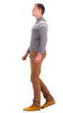 Side view of going man in sweater and brown jeans. Stock Photo