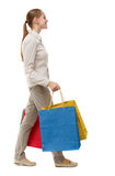 Side view of going  woman  with shopping bags . Stock Images