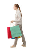 Side view of going  woman  with shopping bags . Royalty Free Stock Images