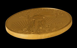 Side view of Gold Eagle one ounce coin. Isolated view of the side of a one ounce gold eagle coin minted in the USA royalty free stock images