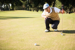 Side view of golfer crouching and looking his ball Stock Images