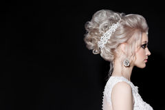 Side view of gorgeous blonde in wedding dress with shiny earrings and accessories in hair. Stylish bride haircut of curly blonde h Royalty Free Stock Photos