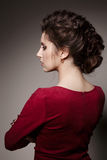 Side view of gorgeous of brunette woman with stylish haircut of curly hair turned back, posing with crossed arms. Brunette girl we Royalty Free Stock Photos