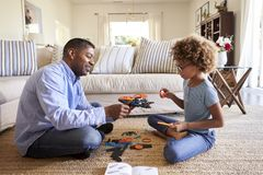 Side view of grandad and granddaughter sitting opposite each other cross legged on the floor in the living room constructing a mod. El robot together, close up stock image