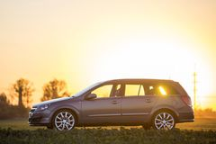 Side view of gray silver empty car parked in countryside on blurred rural landscape and bright orange clear sky at sunset copy stock photography