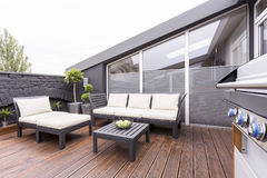 Stylish terrace with garden furniture. Side view of grill on stylish terrace with wooden board floor and bright garden furniture Stock Photography
