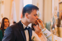 The side view of the groom kissing the golden wedding ring held by the priest. The side view of the groom kissing the golden wedding ring held by the priest Royalty Free Stock Images