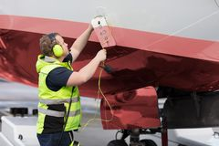 Ground Staff Member Adjusting Communication Cable On Outer Airpl. Side view of ground staff member adjusting communication cable on outer airplane panel at Royalty Free Stock Photos