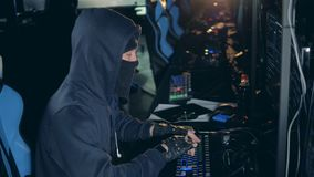 Side view of a hacker in disguise working with computers. 4K stock footage