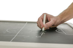 Hand writing a soccer game strategy. Side view of a hand writing a soccer game strategy on a blackboard. Over white background Stock Images
