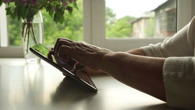 SIDE VIEW: The hands of Aged woman using a digital tablet PC at home stock video