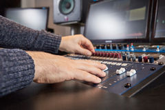 Side view of hands of audio engineer mixing on console Stock Images