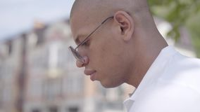 Side view of handsome bald thoughtful middle eastern man sitting on the street. Leisure outdoors. Concept of stock video