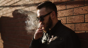 Side view of handsome bearded man smoking Stock Photography