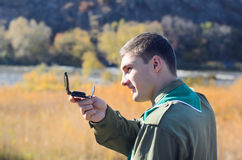 Side View of Handsome Boy Scout Navigating Compass. Close up Side View of a Young Handsome Male Scout Navigating Compass At the Field Stock Images