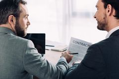 Side view of handsome businessmen looking at each other. In office royalty free stock image