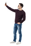 Side view of handsome casual man with sunglasses taking selfie with cell phone. Full body length portrait isolated over white studio background Royalty Free Stock Photography