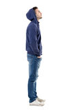 Side view of handsome confident cool young guy with hoodie on head looking up. Full body length portrait isolated over white studio background royalty free stock photography