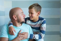 Side view of handsome father and his cute son looking at each other and smiling while spending time together at home. Blue eyes. And plenty blue color tones stock photography