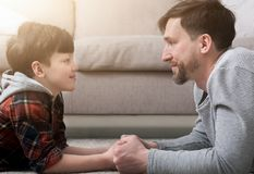 Side view of handsome father and son looking at each other. While spending time together at home Royalty Free Stock Photo