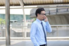 Side view of handsome young Asian business man talking on phone at urban building city background. stock photo