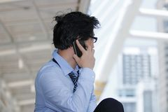 Side view of handsome young Asian businessman talking mobile smart phone at urban building background. Unemployment business conce royalty free stock photos