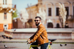 Side view of handsome young bearded man in sunglasses looking away while riding on his bicycle outdoors. Stock Photo