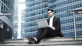 Side view of a handsome young businessman working with a laptop outside stock footage