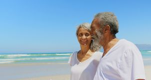 Side view of happy active senior African American couple walking on beach in the sunshine 4k
